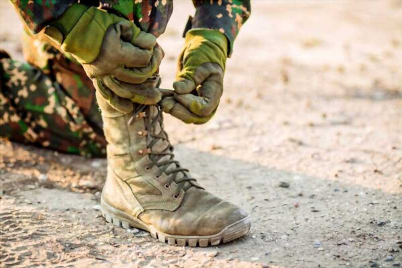 best military boots in seating pose to bind a laces