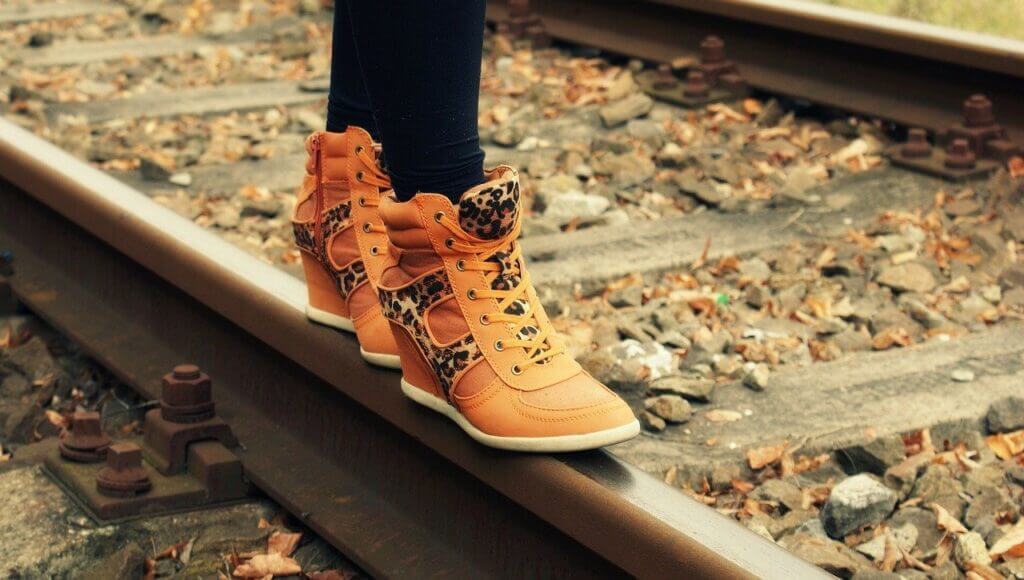 Orange Boots standing on railway track