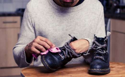 Combat Boots with men cleaning with clothe