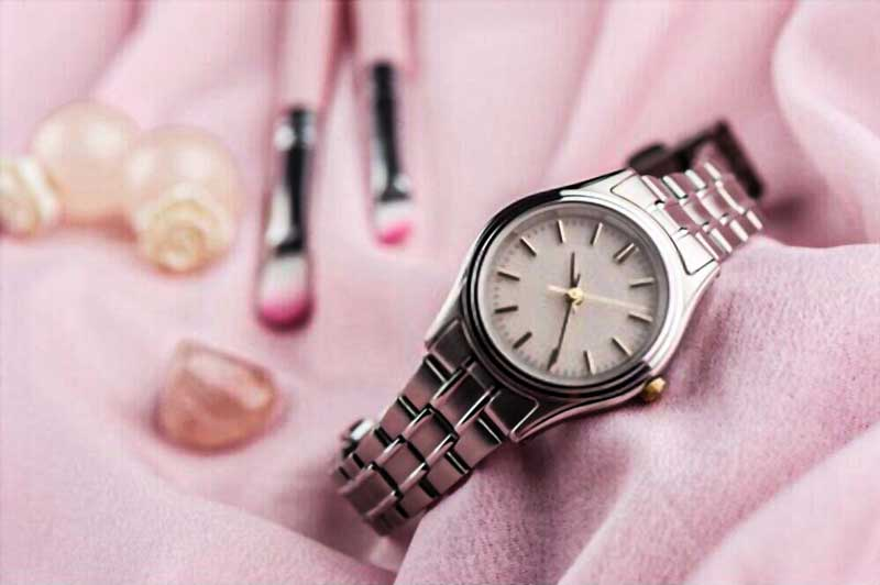 watches for women review in pink background with makeup kit